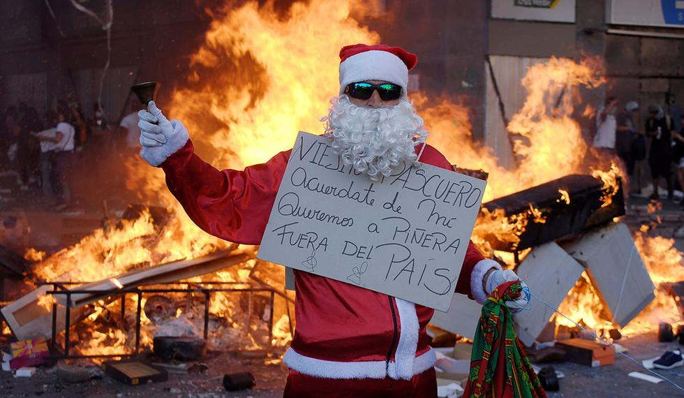 """Un manifestante sostiene un cartel que dice """"Viejito pascuero, acuérdate de mi, queremos a Piñera fuera del país"""", durante una protesta contra el gobierno de Chile en el centro de la ciudad de Concepción. (Foto: Reuters)"""