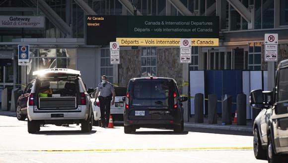 Agentes de la Real Policía Montada de Canadá registran filas de carritos de equipaje mientras las pantallas bloquean un área de la acera después de un tiroteo afuera de la terminal de salidas internacionales en el Aeropuerto Internacional de Vancouver, en Richmond, Columbia Británica, el domingo 9 de mayo de 2021 (Foto: Darryl Dyck / The Canadian Press vía AP)