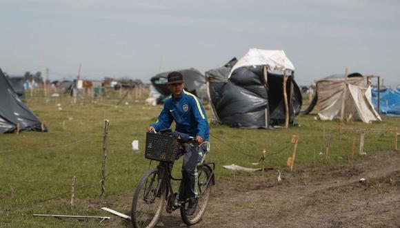 Un joven circula en bicicleta por un camino de tierra hecho por los vecinos, en la localidad de Guernica, a 30 km de Buenos Aires (Argentina). (EFE/Juan Ignacio Roncoroni).
