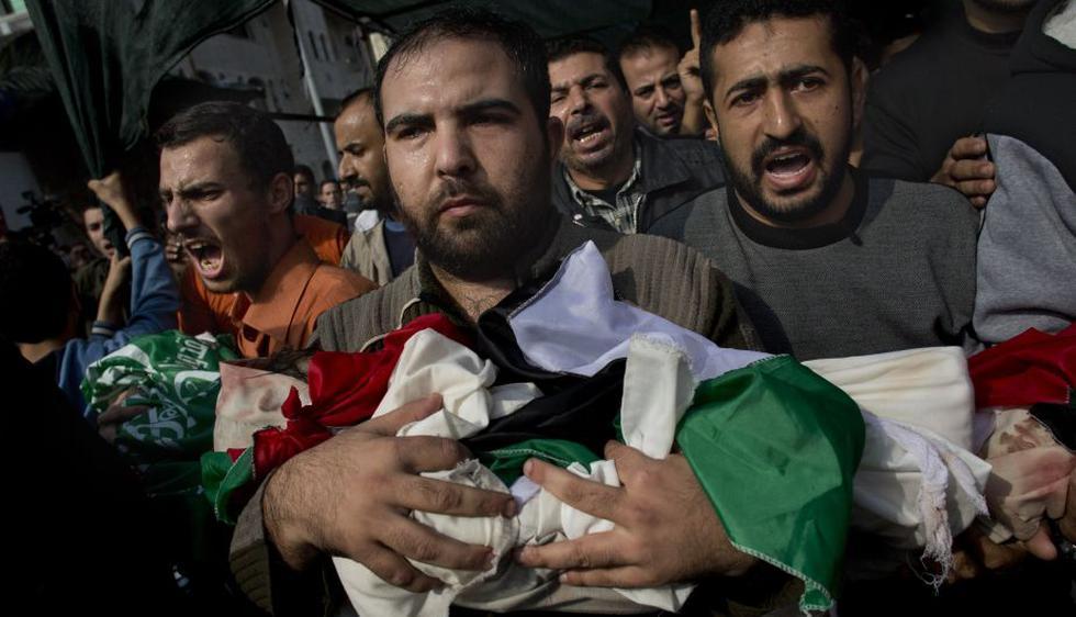 Palestinos cargan cuuerpo de un bebé de la familia Dallu muerto por bombardeo israelí. (AP)