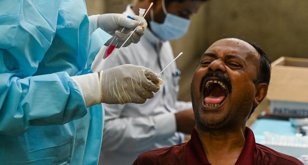 Un trabajador de la salud toma una muestra de un hisopo de un hombre para una prueba de coronavirus Covid-19 en un centro de salud en Nueva Delhi, India. (Foto de Prakash SINGH / AFP).
