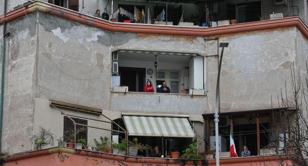 """Los ciudadanos  saludan y aplauden durante un flashmob """"Un applauso per l'Italia"""" (Un aplauso para Italia) en el distrito de Garbatella en Roma el 14 de marzo de 2020. (AFP)."""
