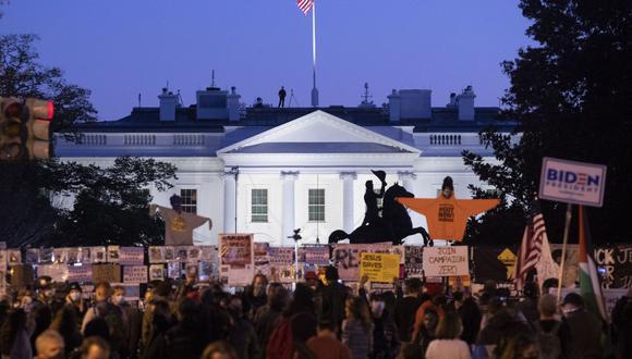 La Casa Blanca se ve al anochecer mientras la multitud se reúne en Black Lives Matter Plaza en Washington, DC, EE.UU. (EFE/MICHAEL REYNOLDS).