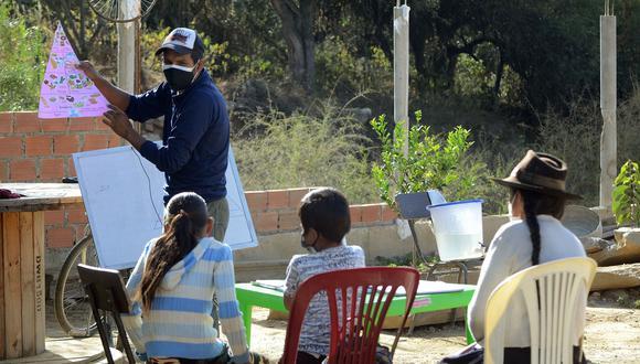 Un profesor en Cochabamba da clases en la casa de unos niños. (AFP)