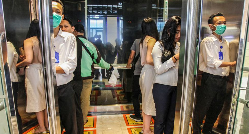 La gente se para en plazas designadas dentro de un elevador para garantizar el distanciamiento social en un centro comercial en Medan, Sumatra del Norte. (Foto: AFP/Ivan Damanik)