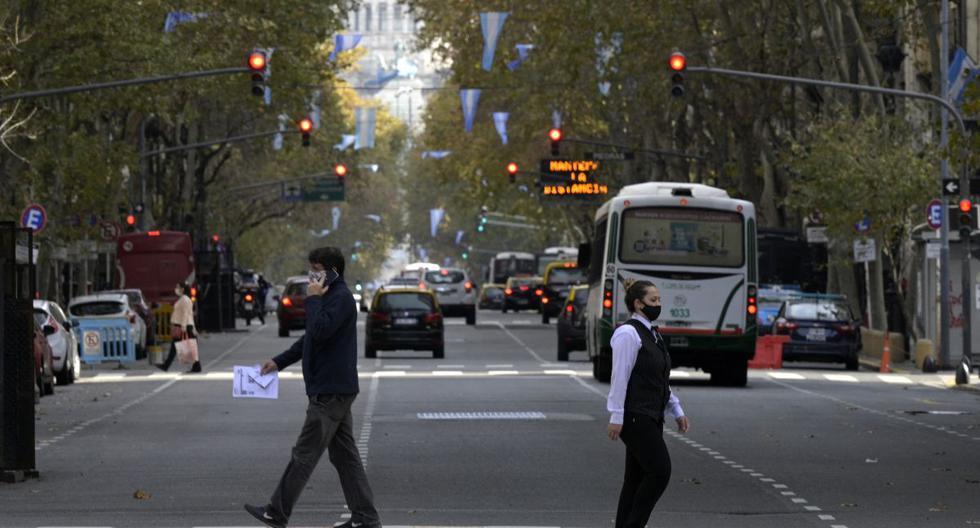 La gente cruza la Avenida de Mayo en Buenos Aires, el 28 de mayo de 2021, en medio de la pandemia de coronavirus. (Foto de JUAN MABROMATA / AFP).
