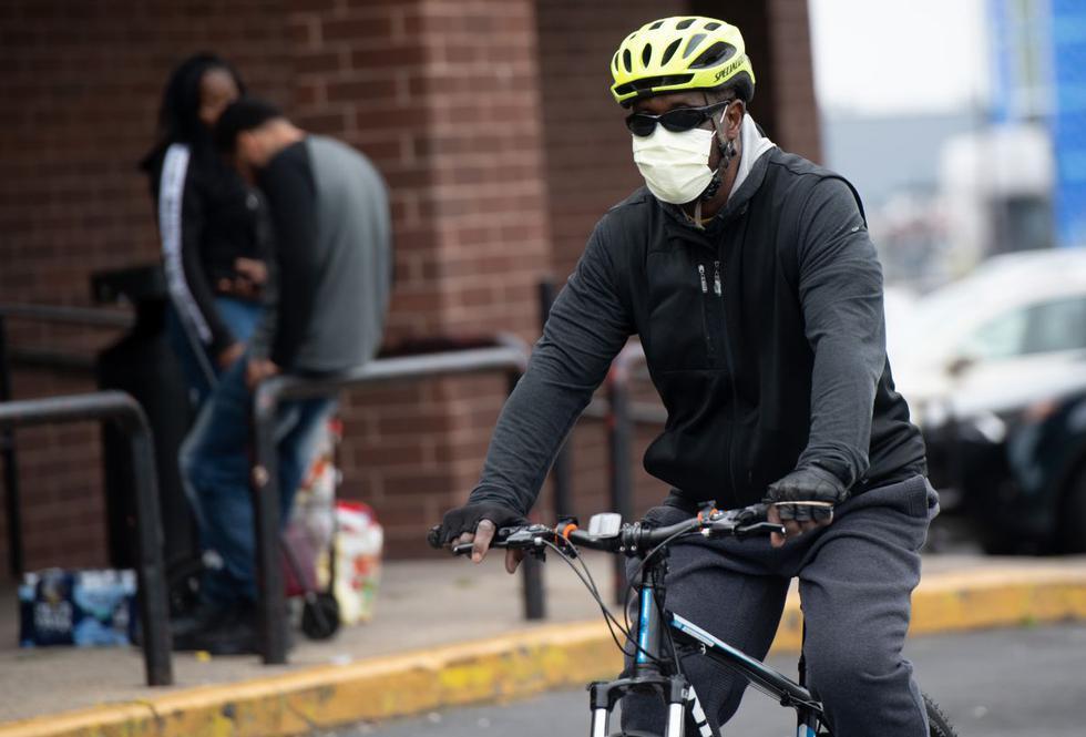 Un hombre, con una máscara para tratar de prevenir la propagación de COVID-19, conocido como coronavirus, llega en bicicleta a un supermercado en Estados Unidos. (Foto: AFP/Saul Loeb)
