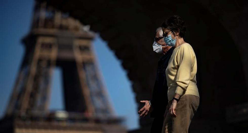 Dos peatones que usan mascarillas protectoras contra el coronavirus disfrutan del cálido clima primaveral mientras cruzan el puente Bir Hakeim, cerca de la Torre Eiffel, en París, Francia. (EFE / EPA / IAN LANGSDON).