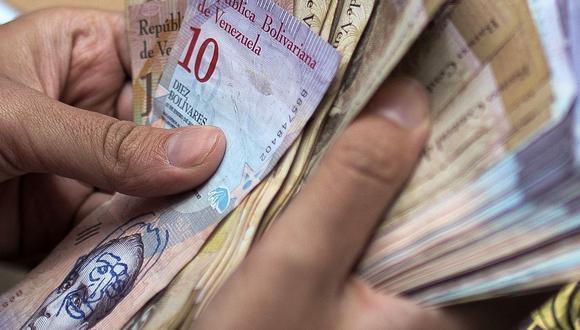 Imagen referencial que muestra a una persona sosteniendo unos bolívares soberanos en Venezuela. (Foto: AFP)
