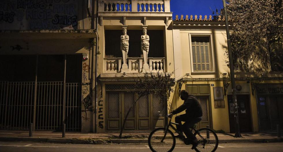 Un hombre monta su bicicleta en una calle vacía en el centro de Atenas (Grecia), el 9 de febrero de 2021. (LOUISA GOULIAMAKI / AFP).