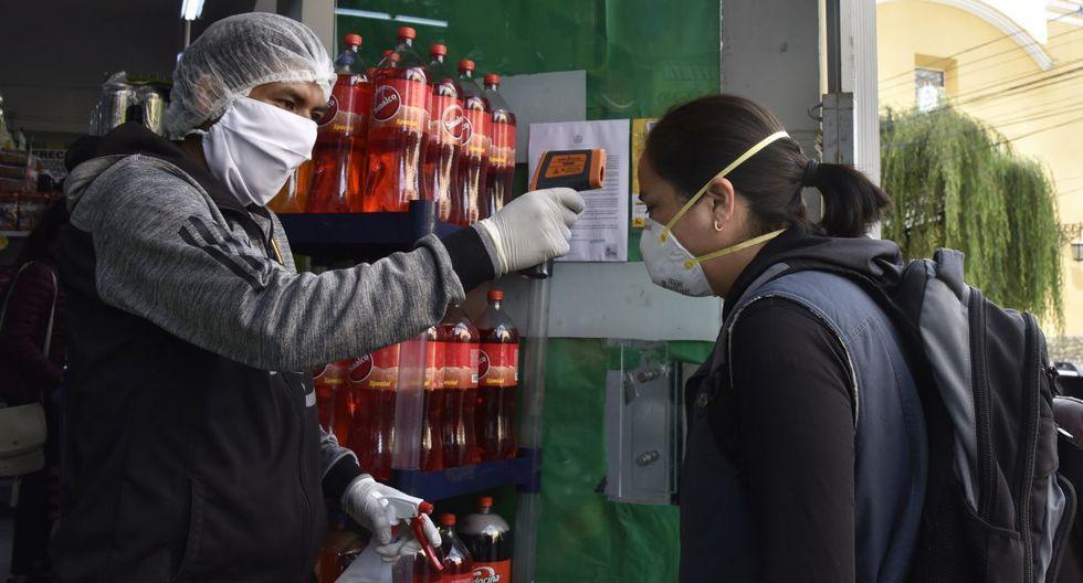 Un trabajador verifica la temperatura de un cliente en una entrada al mercado como medida preventiva contra la propagación del nuevo coronavirus, COVID-19, en un mercado en La Paz, Bolivia. (Foto: AFP)