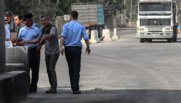Oficiales de seguridad palestinos revisan los documentos de los conductores en la entrada del cruce Kerem Shalom, el principal punto de paso para los bienes que ingresan a Gaza. (Foto: AFP)