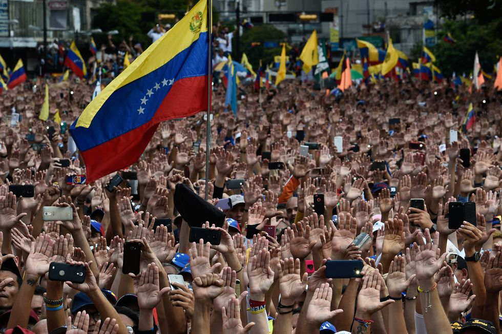 La gente levanta la mano durante una manifestación masiva de oposición contra el presidente Nicolás Maduro. Imagen del 23 de enero de 2019. (Federico PARRA / AFP).