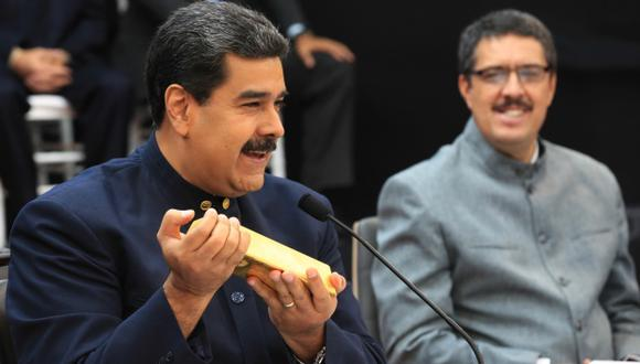 Nicolás Maduro habla mientras sostiene un lingote de oro junto al ministro venezolano de Economía y Finanzas, Ramon Lobo. (Foto: AFP)