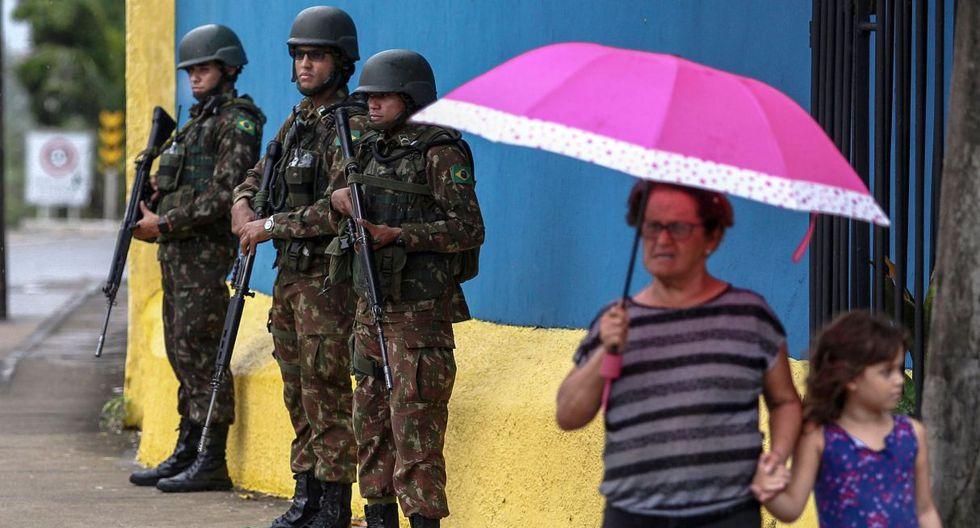 Una mujer junto a una niña es vista en una calle de Ceará. En la parte de atrás, aparecen tres soldados realizando guardia. (AFP).