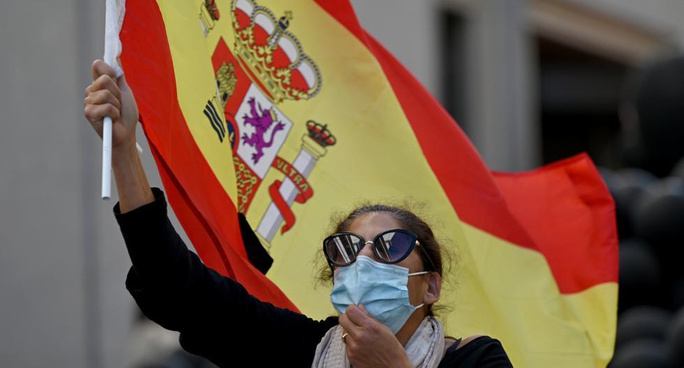 Una mujer ondea una bandera española mientras miembros del grupo de extrema derecha Resiste España se reúnen para una manifestación contra el manejo del gobiern del brote de coronavirus en la nación en Madrid, el 12 de octubre de 2020. (GABRIEL BOUYS / AFP).