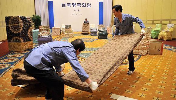 Trabajadores desmantelan los ambientes donde iba a llevarse a cabo el encuentro. (AFP)