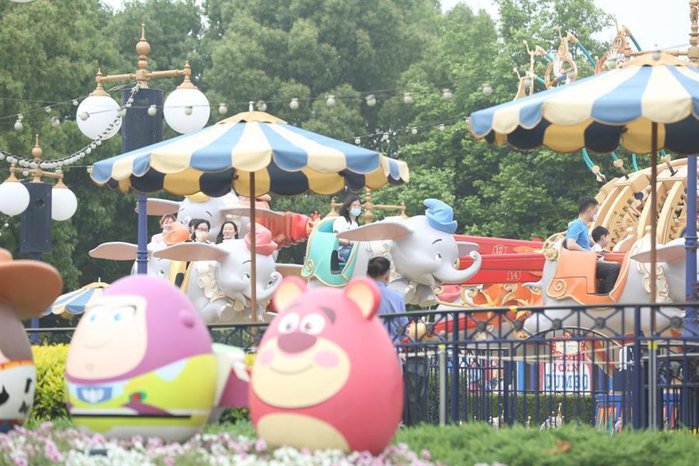 Las personas que usan máscaras protectoras disfrutan de un paseo en el parque temático Disneyland, en Shanghai. (EFE)