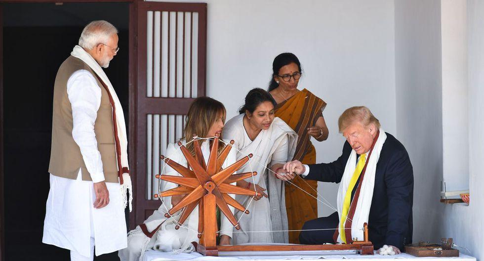 El presidente de los Estados Unidos, Donald Trump, sostiene una cuerda mientras revisa un charkha, o rueca, mientras la Primera Dama Melania Trump  y el Primer Ministro de la India, Narendra Modi observan durante su visita al Gandhi Ashram. (AFP)
