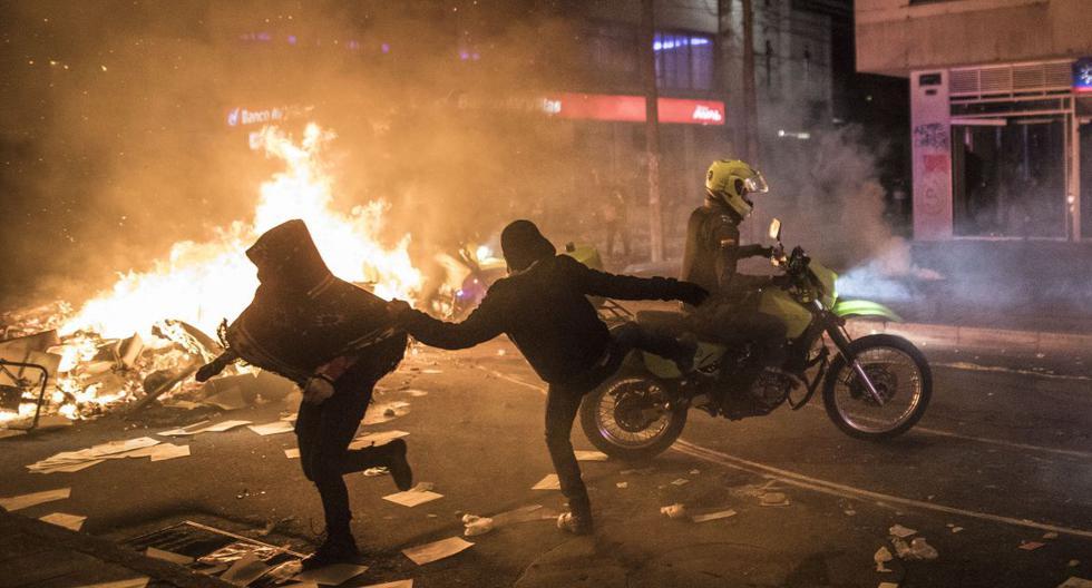 Imagen referencial. Un manifestante patea a un oficial de policía durante las protestas en Bogotá. (AP/Ivan Valencia).