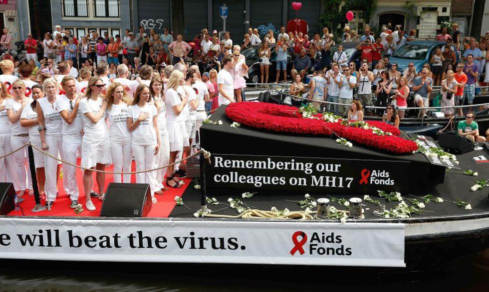 El desfile por los canales de la capital holandesa estuvo encabezado por una barco que portaba un lazo rojo hecho con flores en recuerdo de los expertos en la lucha contra el sida. (EFE)
