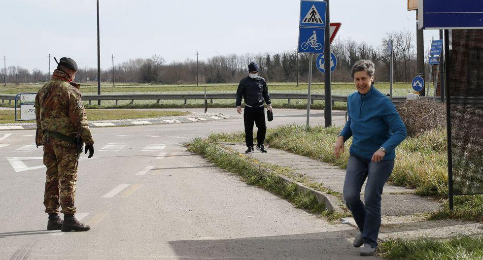 Una mujer camina cerca a un puesto de control en Turano Lodigiano, donde los oficiales recomiendan a los ciudadanos ir a sus casas. (AP).