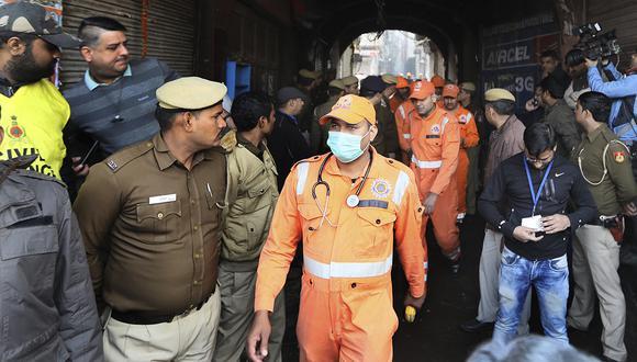 Agentes médicos y policías salen del lugar de un incendio en un callejón, enredado en cables eléctricos y demasiado estrecho para que los vehículos puedan acceder, en Nueva Delhi, India. (Foto: AP)
