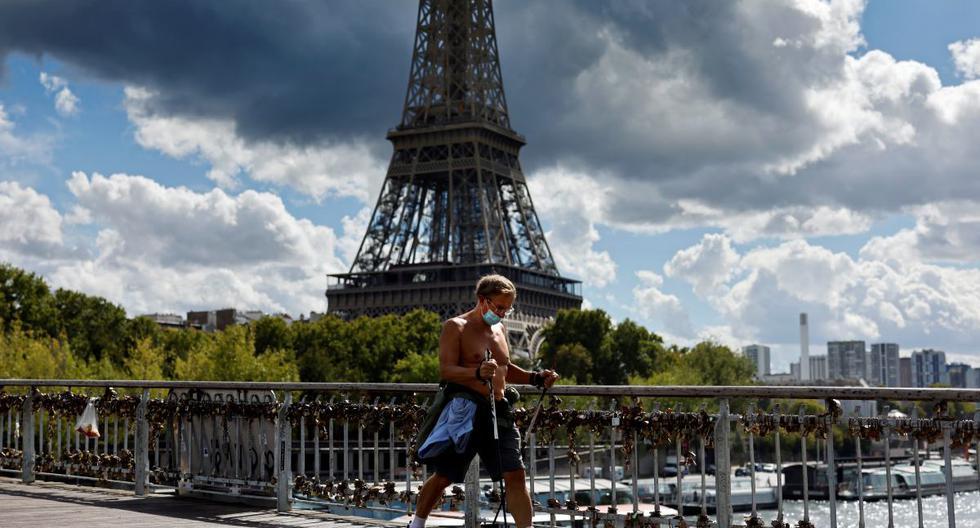 Un hombre con una máscara protectora pasa por delante de la Torre Eiffel en París, el 28 de agosto de 2020. (Thomas COEX / AFP).