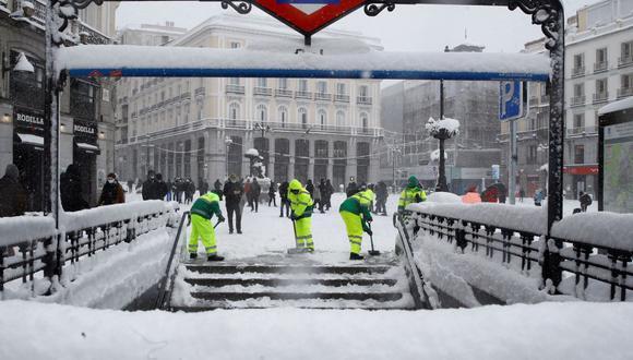 Operarios trabajan para retirar nieve y mejorar la circulación en la Puerta del Sol en Madrid, España. (EFE/ Ballesteros).