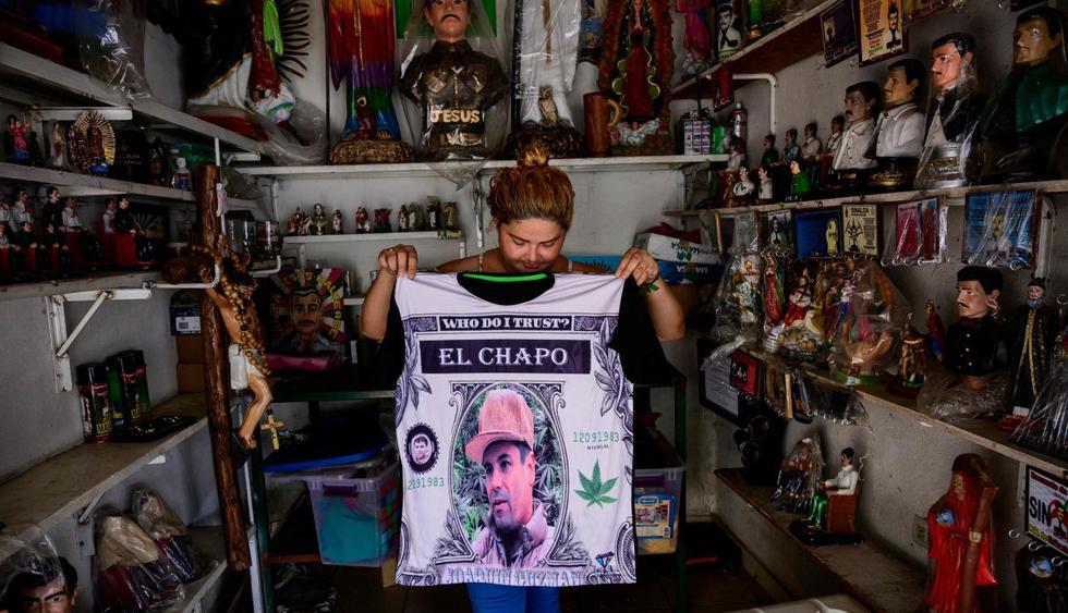 """Vendedora muestra una camisa que representa un retrato de Joaquín """"El Chapo"""" Guzmán en una tienda al lado de la capilla del narco Jesús Malverde en Culiacán. (Foto: AFP)"""