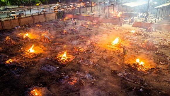 Hombres alrededor de las piras ardientes de las víctimas que perdieron la vida debido al coronavirus en un campo de cremación en Nueva Delhi. (Foto: AFP)
