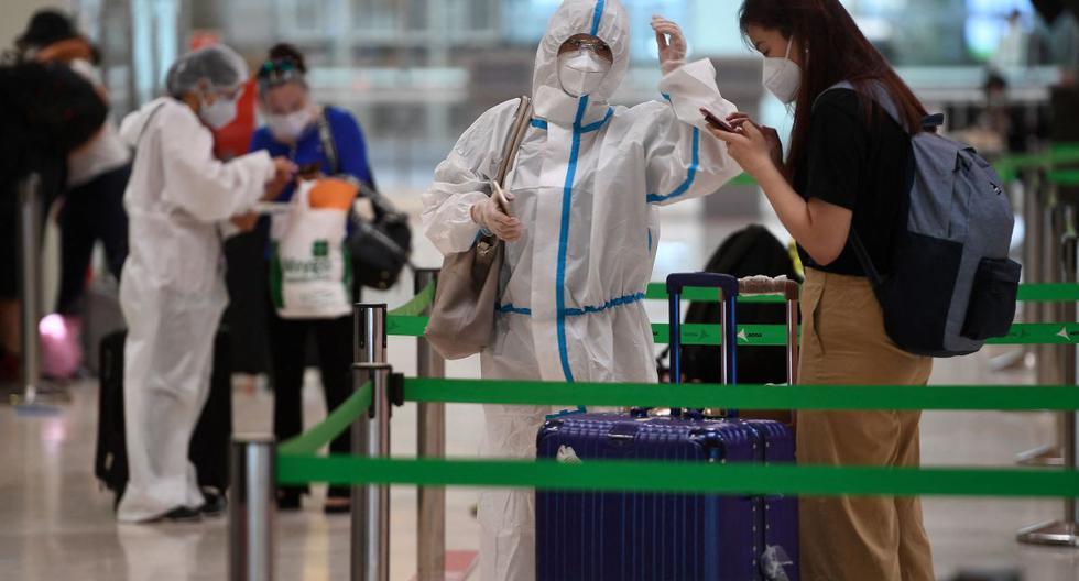 Un pasajero con un traje de protección espera para registrarse para un vuelo en el aeropuerto de Barajas, en Madrid (España), el 20 de junio de 2020. (PIERRE-PHILIPPE MARCOU / AFP).