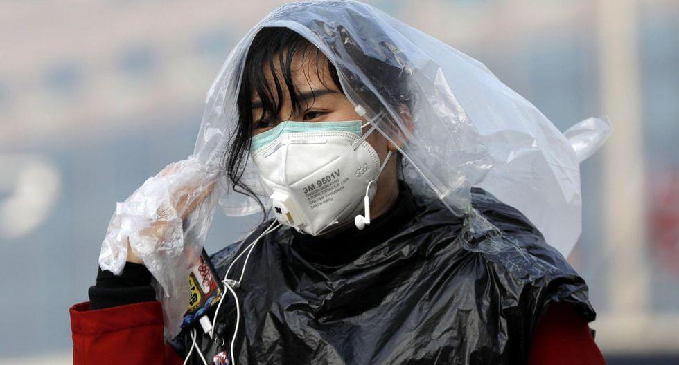 Una mujer que lleva una máscara se cubre la cabeza con una bolsa de plástico en la estación de trenes de Beijing. (EFE).