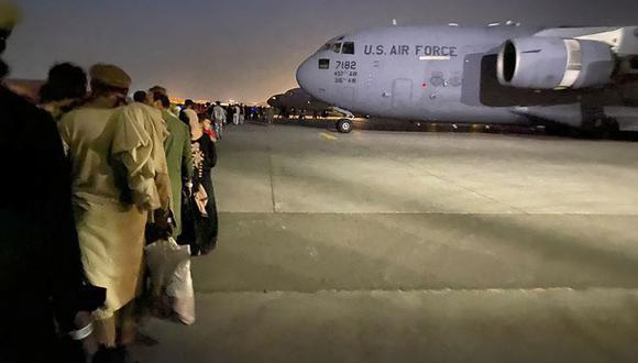 Los afganos hacen cola y abordan un avión militar estadounidense para salir de Afganistán, en el aeropuerto militar de Kabul el 19 de agosto de 2021. (Foto de Shakib RAHMANI / AFP).