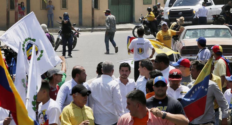 Una foto distribuida por la oficina de prensa de la oposición Juan Guaido muestra a un hombre enmascarado  apuntando con un arma a un grupo como el líder de la oposición Juan Guaido. (EFE).