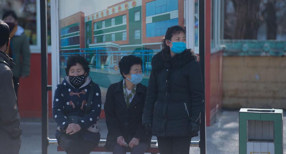 Los pasajeros vestidos con máscaras esperan en una estación de tranvía en Pyongyang. (AFP).