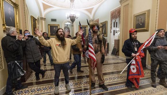 Los partidarios de Donald Trump en el Capitolio. En el centro está Jake Angeli, con sombrero de piel con cuernos. (Foto AP / Manuel Balce Ceneta).