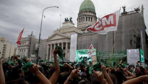 Activistas por el derecho al aborto celebran que la cámara baja de Argentina apruebe un proyecto de ley que legalizaría el aborto fuera del Congreso en Buenos Aires, Argentina. (Foto AP / Natacha Pisarenko).