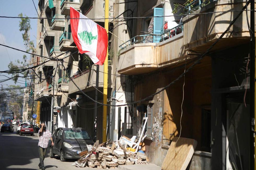 Un hombre camina por una calle en el barrio parcialmente destruido de Mar Mikhael en Beirut (Líbano). (AFP / PATRICK BAZ).