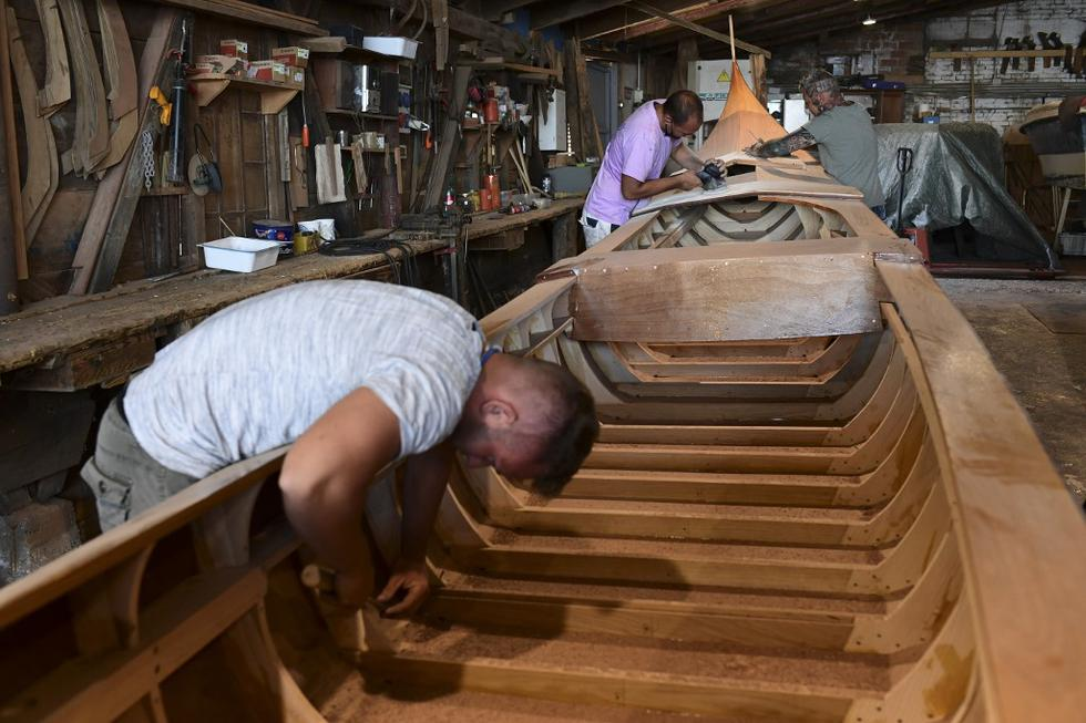 Dos constructores de góndolas son fotografiados trabajando en una góndola en el astillero Roberto Dei Rossi, en Venecia. (MIGUEL MEDINA / AFP)