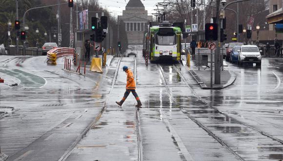 Un trabajador cruza la calle en el distrito comercial central de Melbourne. (William WEST/AFP).
