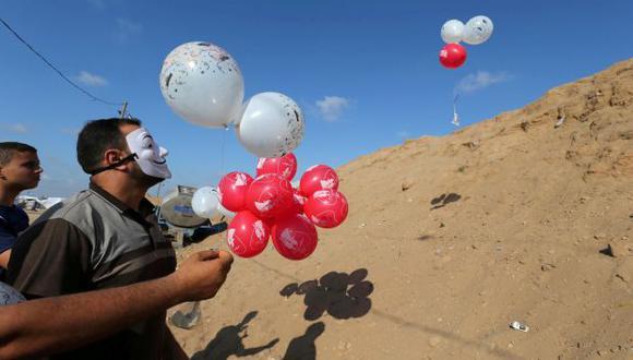 Los palestinos llevan globos cargados con material inflamable para ser arrojados al lado israelí, cerca de la frontera entre Israel y Gaza en el centro de la Franja de Gaza. (Foto: Reuters)