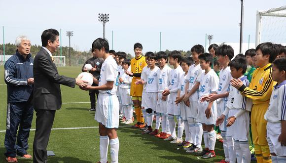 Shinzo Abe visita a un equipo juvenil de fútbol en Fukushima. (Foto: AFP)