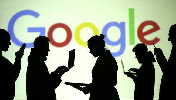 Las siluetas de los usuarios de dispositivos móviles se ven junto a la proyección de una pantalla del logotipo de Google. (Foto: Reuters)