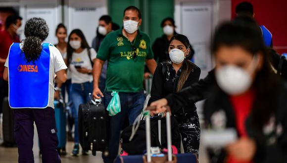 Los pasajeros usan mascarillas como medida preventiva contra la propagación del coronavirus COVID-19 en el Aeropuerto Internacional de Ezeiza en Buenos Aires. (Foto: AFP)