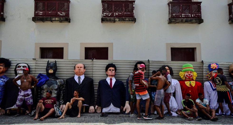 Varias personas descansan este lunes junto a los tradicionales muñecos del Carnaval en Olinda, estado Pernambuco (Brasil). (EFE).