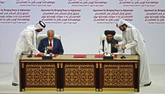 El Representante Especial de los Estados Unidos para la Reconciliación de Afganistán, Zalmay Khalilzad, y el cofundador talibán, Mullah Abdul Ghani Baradar, firman el acuerdo de paz. (AFP).
