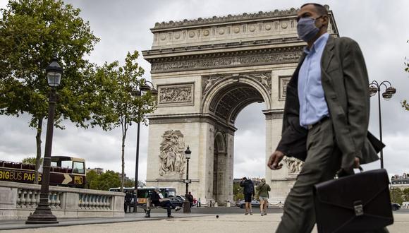 Un hombre con máscara protectora camina por los Campos Elíseos cerca del Arco del Triunfo, en París, Francia. (EFE / IAN LANGSDON).
