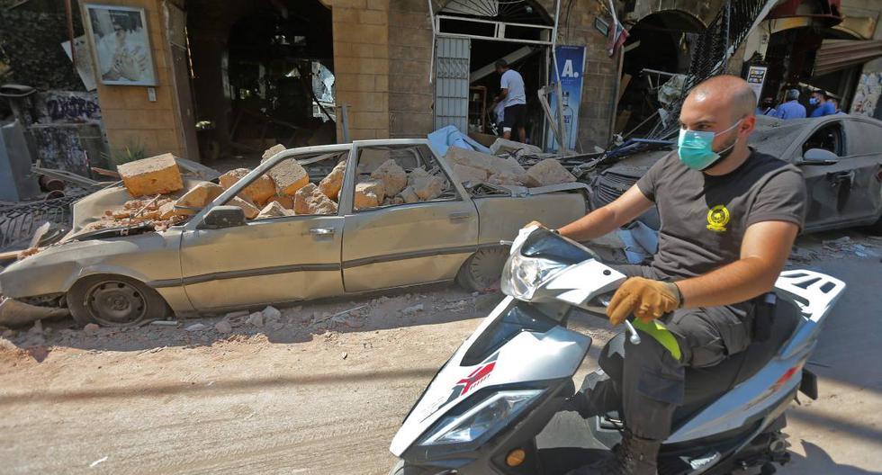 Imagen referencial. Un hombre que llevaba una mascarilla contra el coronavirus conduce su motocicleta frente a autos y tiendas dañadas por la explosión en Beirut, Líbano. (AFP / STR).