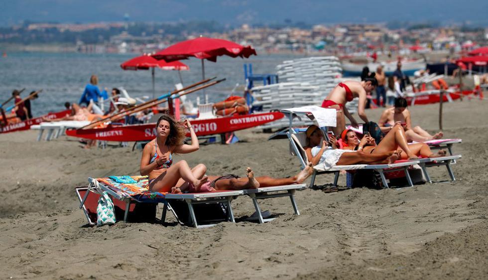 Las personas toman el sol en una playa en Fregene, cerca de Roma, Italia. (REUTERS/Remo Casilli).